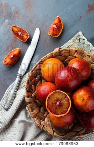 Fresh ripe Sicilian oranges and sliced pieces on a gray concrete background. Selective focus. Top view.