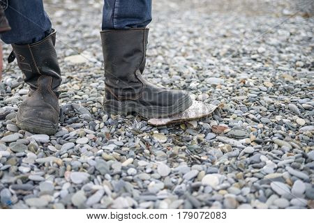 Closeup of man in black hiking boots standing on pebble
