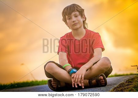 outdoor portrait of young teen boy on sunset natural background