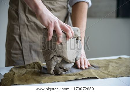 Closeup of man in apron crumpling piece of white clay for sculpting on table