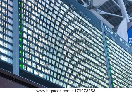 Closeup of blue departure board with destinations and times timetable in airport abstract background