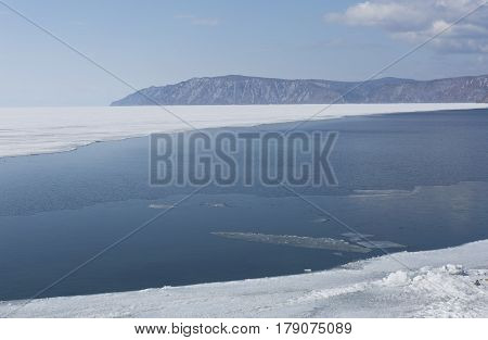 Baikal lake spring landscape view. Snow-covered shore of the lake. Rocky forested coastline. Boundary of ice and open water