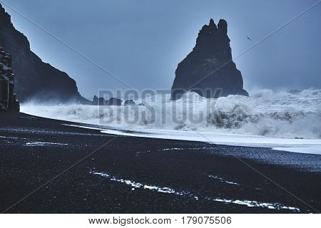 Reynishverfisvegur, Reynisfjara black sand beach with rocks, ocean and dark rain and storm clouds near the village of Vik in Iceland.