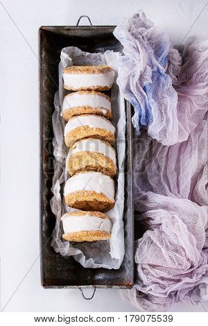 Set of homemade ice cream sandwiches in oat cookies with almond sugar crumbs on baking paper in old metal bowl over gray texture background. Top view with space