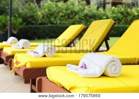 Rolled up towels on yellow sunbeds in pool at resort.