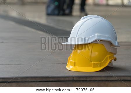 white safety helmets on yellow safety hemets on the cement floor