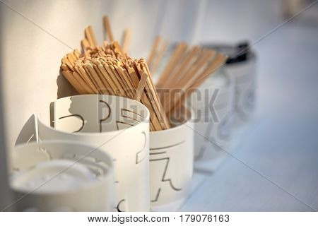 dishware and eating concept - wooden drink stirrers in holder on restaurant table