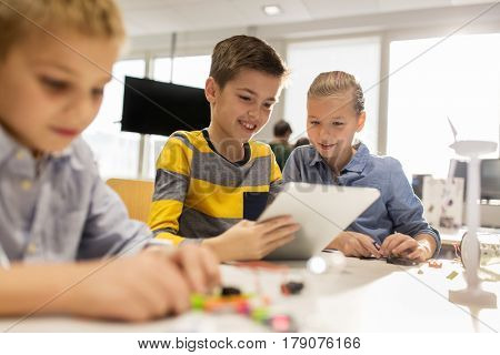education, science, technology, children and people concept - group of smiling kids or students with tablet pc computer programming at robotics school lesson