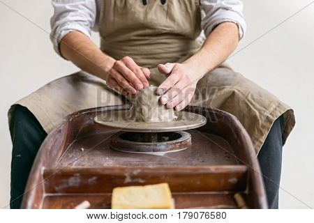 Man in apron working on pottery wheel crafting bowl