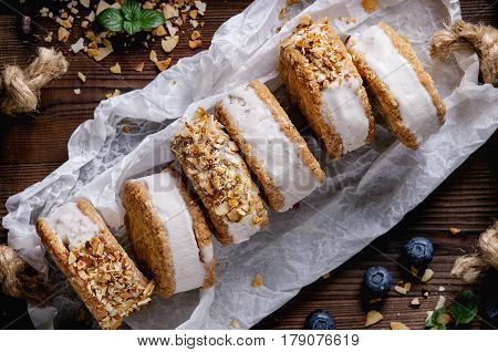 Set of homemade ice cream sandwiches in oat cookies with almond sugar crumbs and blueberries on baking paper over dark wooden texture background. Top view, close up