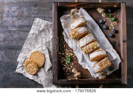 Set of homemade ice cream sandwiches in oat cookies with almond sugar crumbs on baking paper in woden tray over dark metal texture background. Top view with space