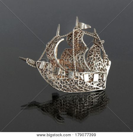 Vintage filigree silver brooch Sailboat on gray background with mirror reflection