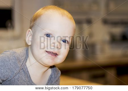 Attentive big-eyed toddler looking at camera on blurred background. Close-up