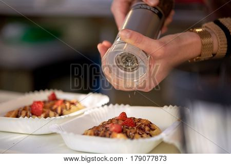 food, cooking, dessert and people concept - close up of cook hands with spice mil spicing strawberry waffle