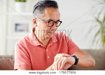 people, punctuality and time concept - asian man looking at his wristwatch at home