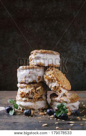 Set of homemade ice cream sandwiches in oat cookies with almond sugar crumbs, blueberries and mint over dark metal texture background. Close up