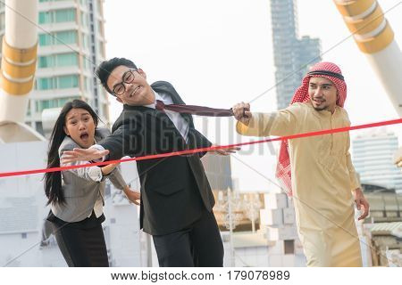 Young businessman trying to catch the red ribbon on the back with an Arabian businessman pulled necktie.