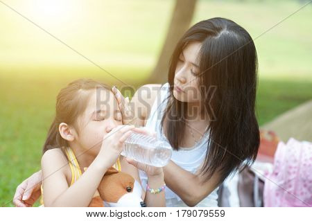 Portrait of Asian mother comforting her crying child in the park, Family outdoor lifestyle.