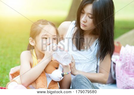 Asian mother comforting her crying child in the park, Family outdoor lifestyle.