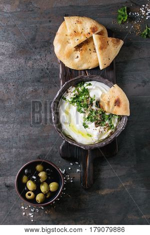 labneh middle eastern lebanese cream cheese dip with olive oil, salt, herbs served with olives, traditional pita bread in terracotta bowl over dark texture metal background. Top view with space