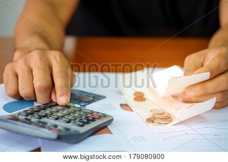 Men are using a calculator to analyze slip credit card.
