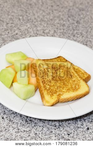Vertical photograph of cooked French Toast with fruit on white plate placed on gray and black marble counter. Copy space above.