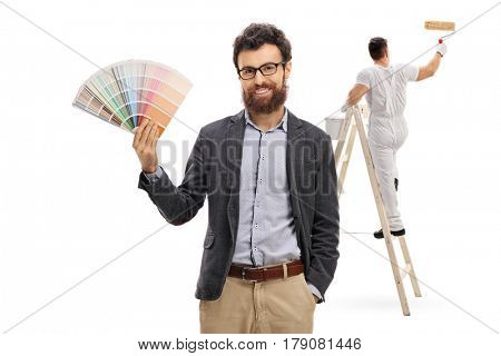 Young man holding a color swatch with a painter painting climbed up a ladder isolated on white background