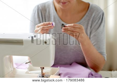 people, needlework and tailoring concept - tailor woman with thread and spool of sewing machine at studio