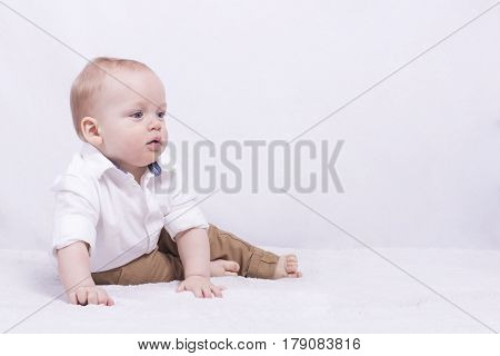 Thoughful big-eyed toddler looking away and sitting on the white blanket. Copy space. Form for a postcard.