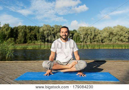fitness, sport, yoga, people and healthy lifestyle concept - smiling man making scale pose lotus variation on mat outdoors on river or lake berth