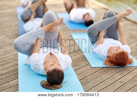 fitness, sport, yoga and healthy lifestyle concept - group of people making half ankle to knee supine pose on wooden berth outdoors