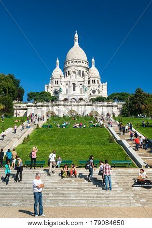 PARIS - SEPTEMBER 24: Tourists visiting the Basilica of the Sacred Heart (Basilique du Sacre-Coeur) on september 24, 2013. A popular landmark the basilica is located at the summit of the butte Montmartre the highest point in the city.