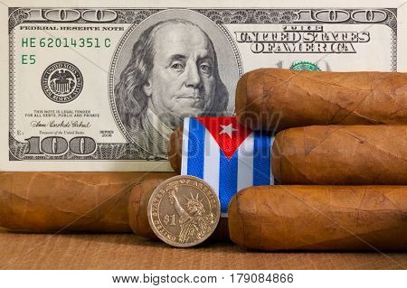 Luxury Cuban cigars with US dollar banknote and coin on the wooden table.