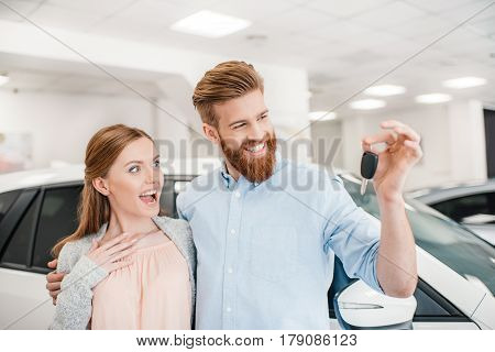 Excited Couple Holding Car Key And Standing At Car In Dealership Salon