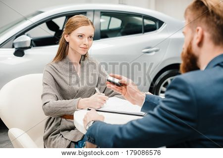 Bearded Salesman Giving New Car Key To Young Woman Signing Papers