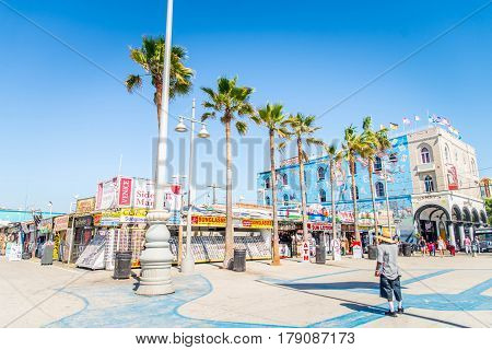 VENICE BEACH USA - SEPTEMBER 29 2016: The crowded Venice Beach Boardwalk. Lots of people are strolling down the boardwalk. On the sides there are several shops and palm trees.