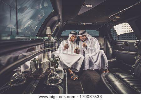 Arabic businessmen in Dubai driving on a limousine