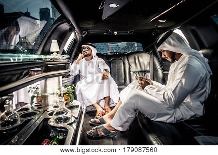Arabic businessmen in Dubai driving on a limousine