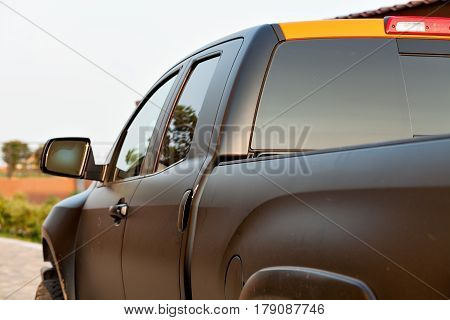The black colored pickup car parked on the road. Horizontal outdoors shot.