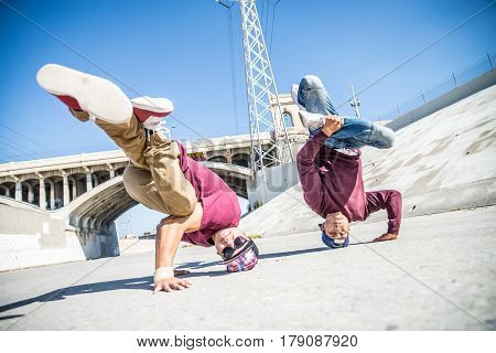 Two boys doing some stunts - Street artist breakdancing outdoors