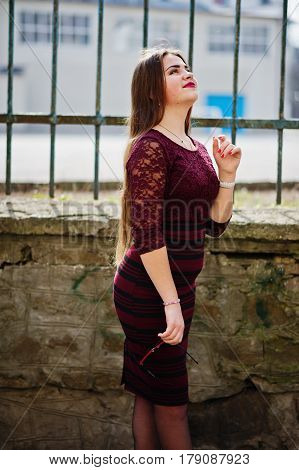Young Chubby Teenage Girl Wear On Red Dress With Sunglasses At Hand Posed Against Iron Fence.