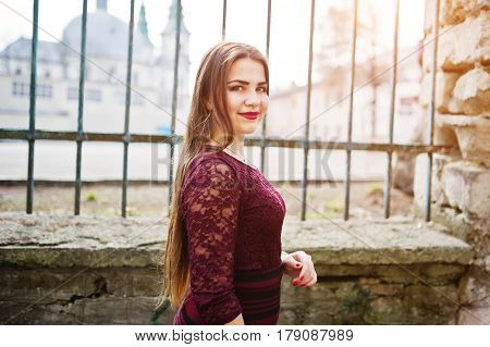 Close Up Portrait Of Young Chubby Teenage Girl Wear On Red Dress Posed Against Iron Fence.