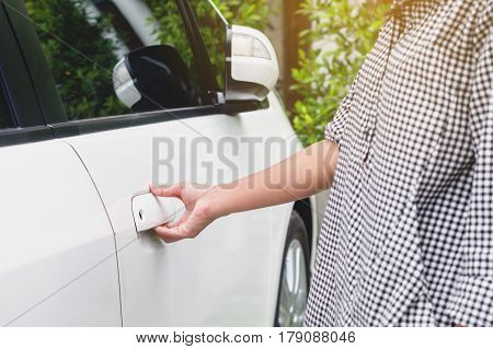 Close up woman hand opening a car door Hand holding door hand to open