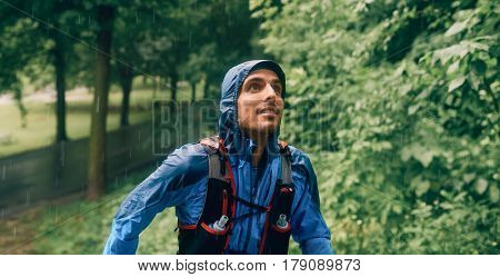 Competitive, athletic young man runs off road outdoors through the woods on a trail on a rainy day wearing sportswear.