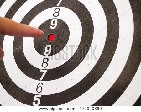 Black and white dart with hand point at center (Concept for target achievement business focus)
