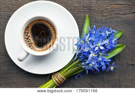 Coffee cup and bouquet of first spring flowers on old rustic wooden table.Coffee mug and blue Scilla flowers.Spring morning,Breakfast,Good morning concept.