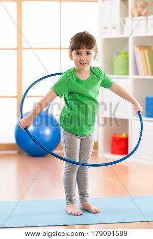 kid girl doing gymnastic with hoop in children room