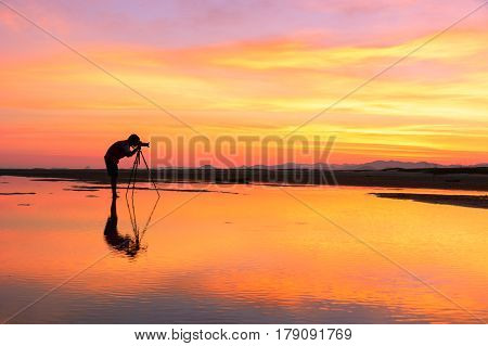 Young Man taking photo with Camera of the view Beautiful sunset at Bang Saphan in winter Thailand