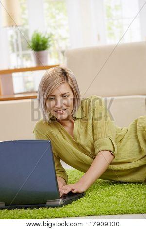 Lächelnde Frau auf Laptop-Tastatur tippen auf Boden zu Hause liegen.?