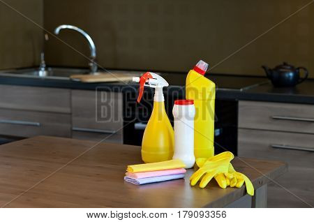 The set of bottles, gloves and dusters for cleaning in the kitchen.